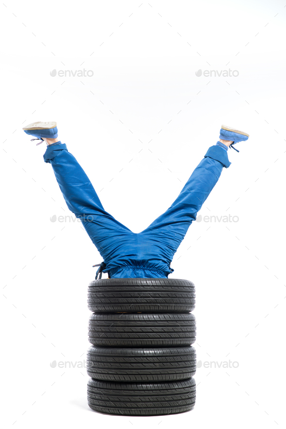 Legs of the worker stick out of the pile of tires - Stock Photo - Images