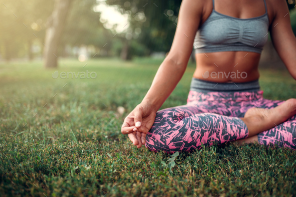 Young woman relax in yoga pose on the grass - Stock Photo - Images