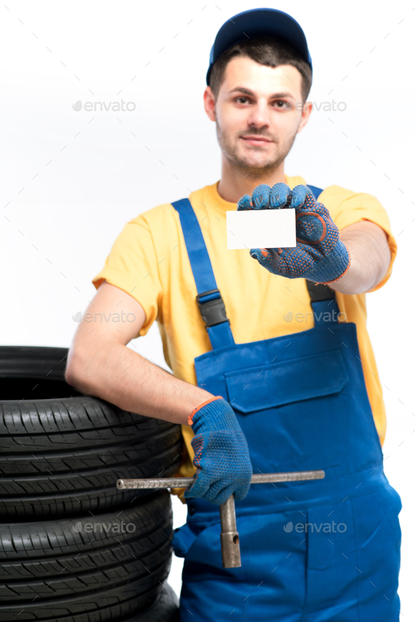 Worker holds tire and empty businesscard in hands - Stock Photo - Images