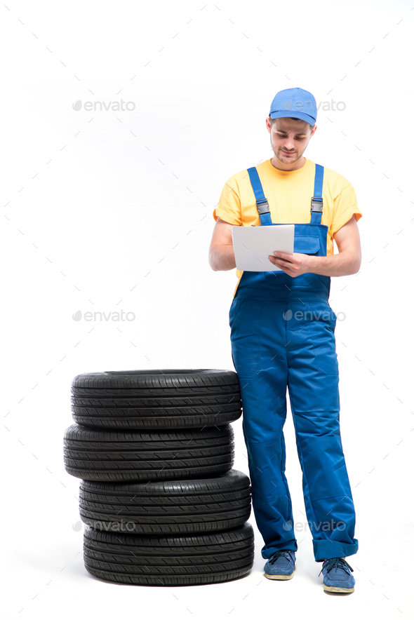 Service worker with notebook against pile of tires - Stock Photo - Images