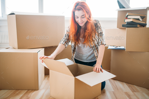 Woman unpacking cardboard boxes in new home - Stock Photo - Images