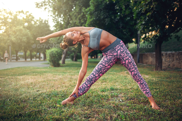 Woman doing yoga exercise in summer park - Stock Photo - Images