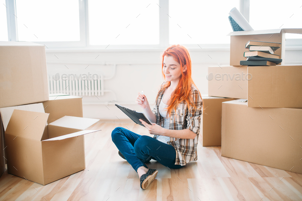 Woman sitting on the floor among cardboard boxes - Stock Photo - Images