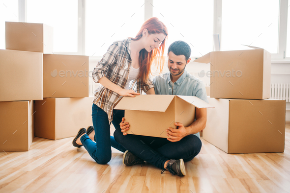 Couple unpacking boxes with property, housewarming - Stock Photo - Images