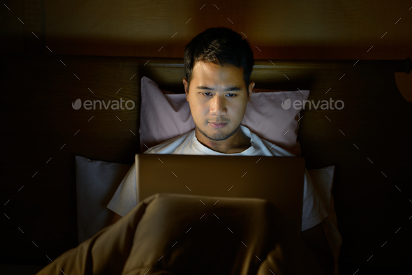 Young man using laptop computer in his bed at night