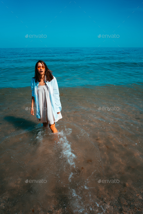 The girl is standing in the sea by the shore - Stock Photo - Images