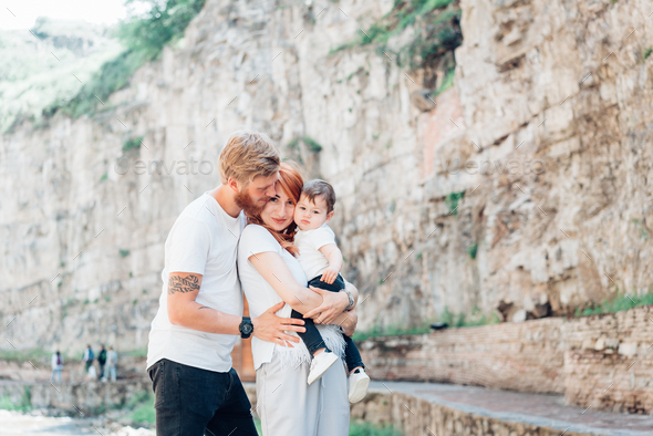 The family standing near a rock wall - Stock Photo - Images