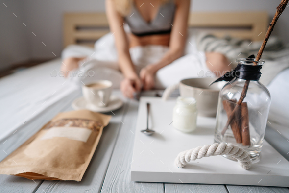 Woman eating cereals in bed - Stock Photo - Images