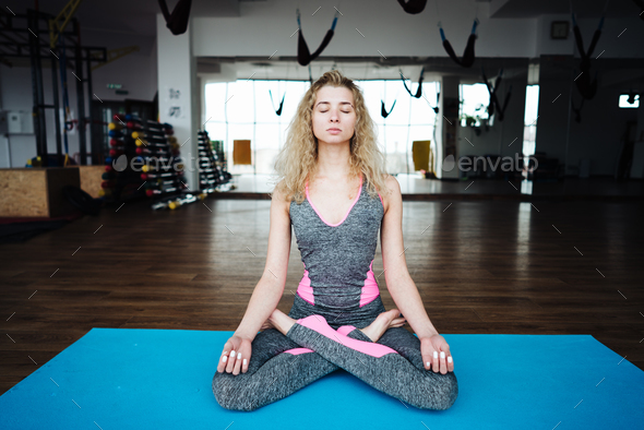 Young slim blond woman in yoga class - Stock Photo - Images