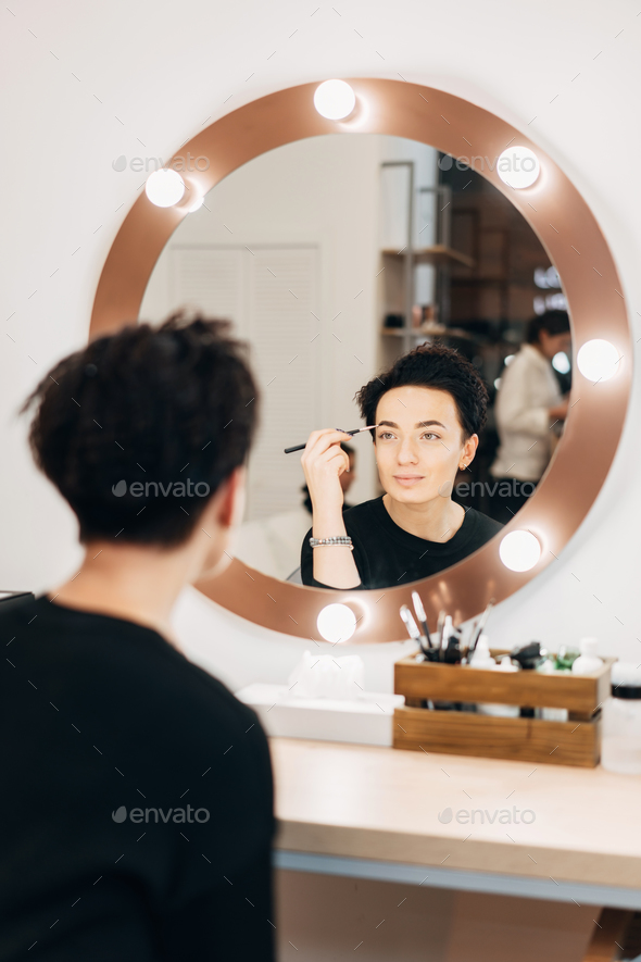 Attractive woman at the mirror in beauty studio - Stock Photo - Images