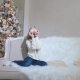 A Young Girl Sits Near a Decorated Christmas Tree, a Guy Approaches and Kisses Her - VideoHive Item for Sale
