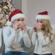 A Young Man and a Beautiful Girl Sit Near a Christmas Tree and Drink Tea - VideoHive Item for Sale