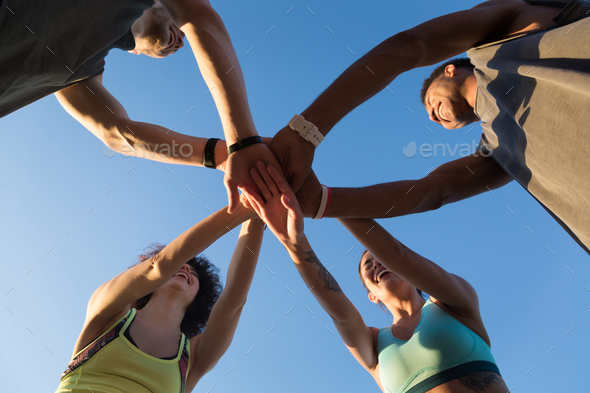 View from below of a group of sporty people in a huddle - Stock Photo - Images