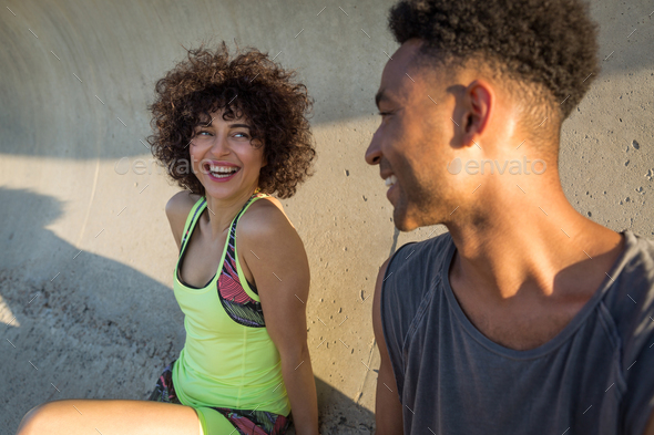 Happy fitness couple in sportswear laughing