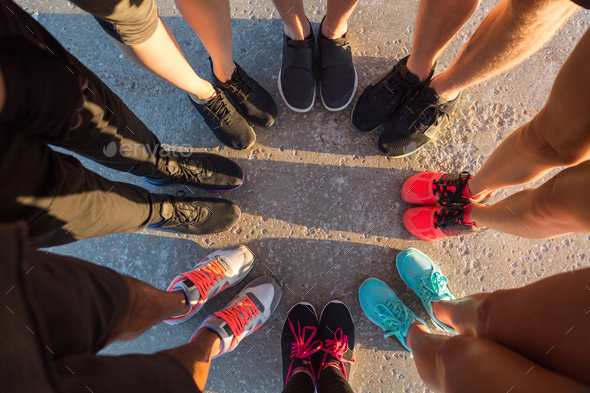 Runners standing in a huddle with their feet together - Stock Photo - Images