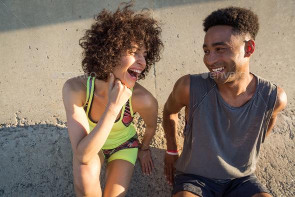 Young happy fitness couple in sportswear talking