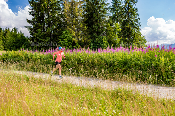 Young woman running on country road in mountains, summer day - Stock Photo - Images