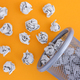 Grey crumpled paper balls rolling out of a trash can - PhotoDune Item for Sale