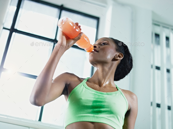 african woman in gym drinking energy drinkAfrican Woman In Gym Drinking Energy Drink