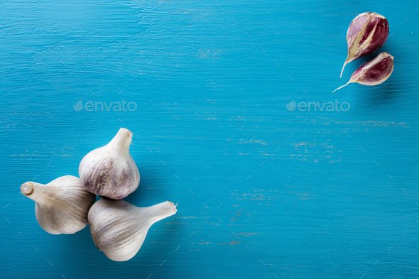 Three heads and cloves of garlic on a wooden table - Stock Photo - Images
