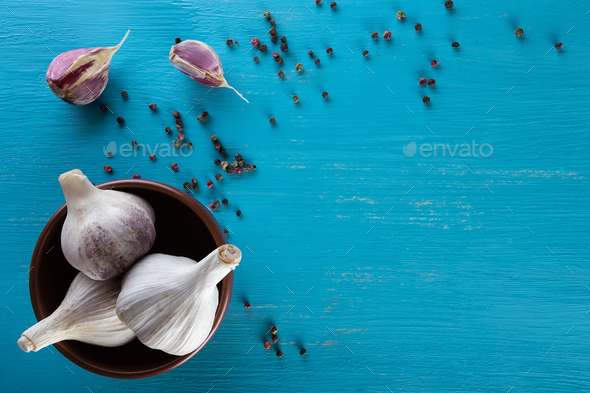 Garlic in plate and pepper on blue wooden table - Stock Photo - Images