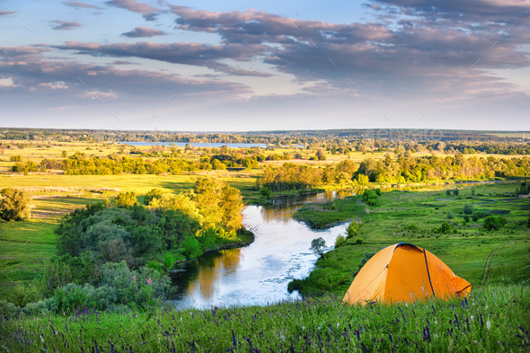 Orange tent on the high bank of the river - Stock Photo - Images