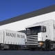 Freight Semi Trucks with MADE IN SWITZERLAND Caption on the Trailer Loading or Unloading
