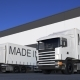Freight Semi Trucks with MADE IN ITALY Caption on the Trailer Loading or Unloading