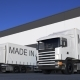 Freight Semi Trucks with MADE IN AUSTRIA Caption on the Trailer Loading or Unloading
