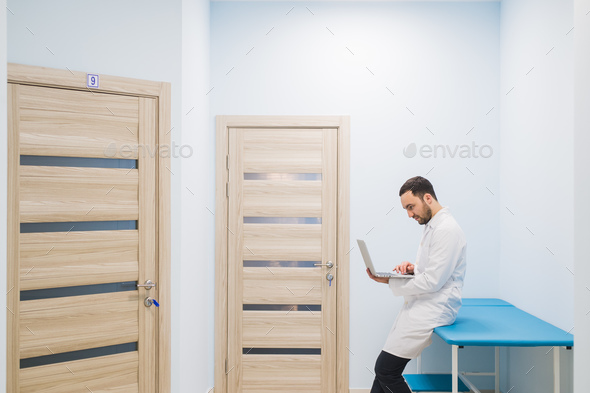 specialist doctor in the corridor of his clinic with his laptop - Stock Photo - Images