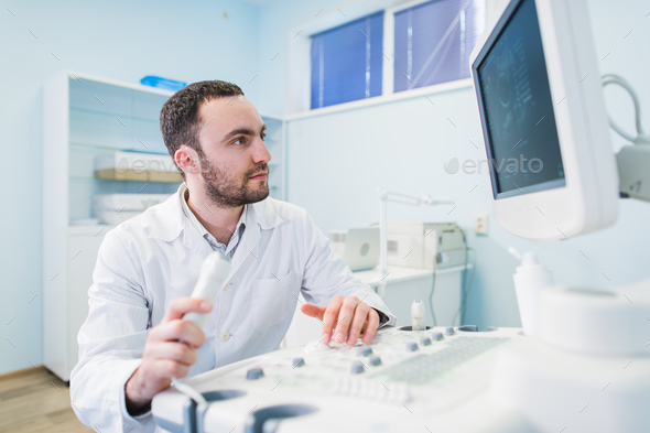 Portrait of a thinking doctor near sceen of medical equipment. - Stock Photo - Images