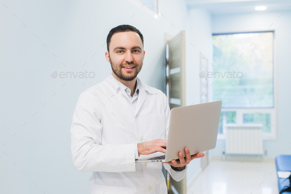 Portrait Of Doctor Holding Laptop, Indoors - Stock Photo - Images