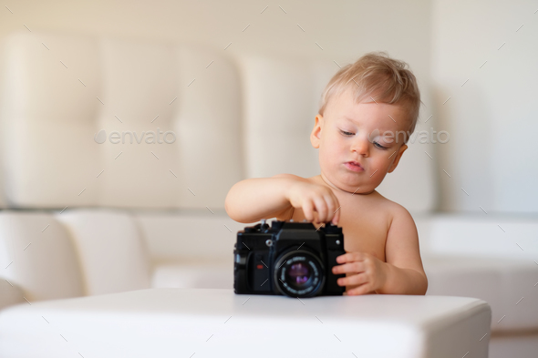Baby boy with blue eyes. Toddler child exploring old camera