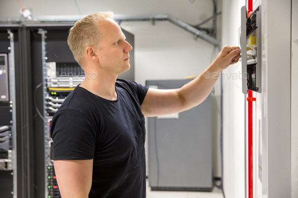 Confident Male Technician Opening Fire Panel In Datacenter - Stock Photo - Images
