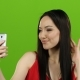 Asian Girl Does Selfie, She Smiles While Looking at the Camera. Green Screen - VideoHive Item for Sale