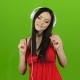 Girl in the Headphones Listens To Classical Music. Green Screen