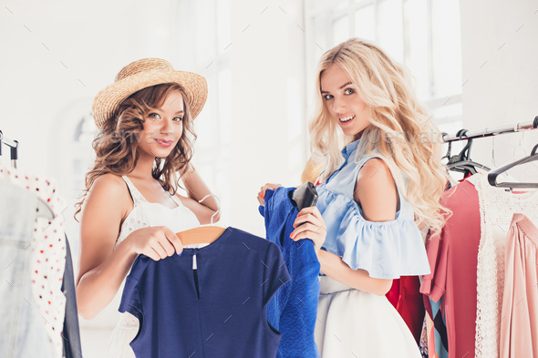 The two young pretty girls looking at dresses and try on it while choosing at shop