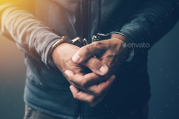 Arrested computer hacker with handcuffs - Stock Photo - Images