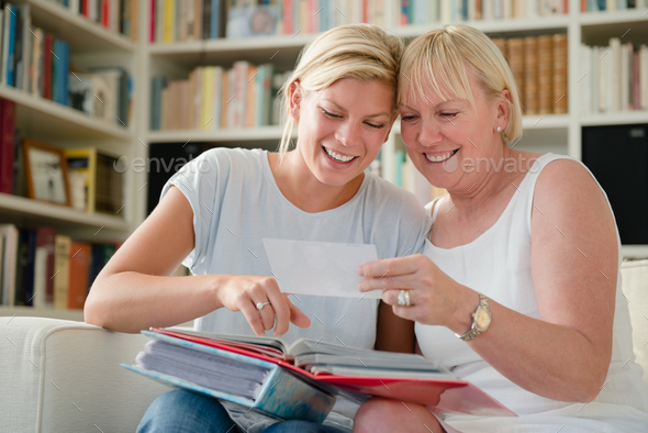 Mother And Daughter Looking At Pictures In Photo Album