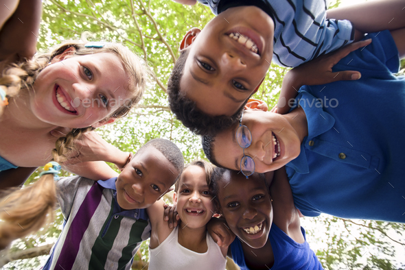 Children Embracing In Circle Around The Camera And Smiling - Stock Photo - Images
