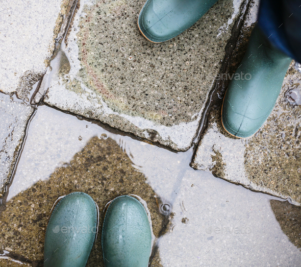 legs in green rubber boots in puddle - Stock Photo - Images