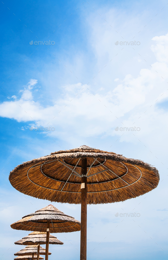 straw parasols and blue sky on beach - Stock Photo - Images