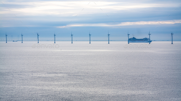 cruise liner near offshore wind farm in morning