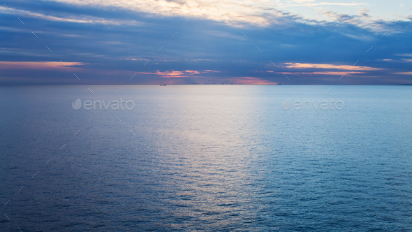 pink sunrise over calm blue Baltic Sea in autumn - Stock Photo - Images