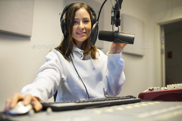 Confident Female Jockey Using Technologies In Radio Studio - Stock Photo - Images