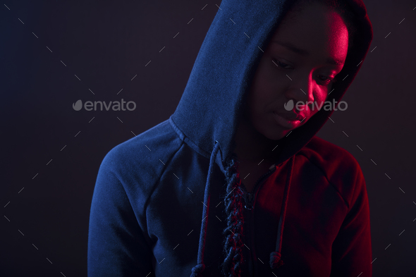 Colorful portrait of thoughtful woman with dark skin wearing hoodie - Stock Photo - Images