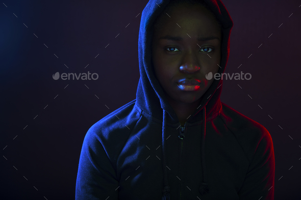 Colorful portrait of a cool woman with dark skin wearing hoodie - Stock Photo - Images