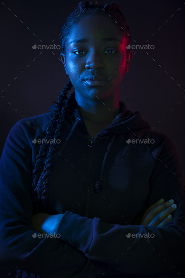 Dark colorful portrait of confident african woman with dark skin - Stock Photo - Images