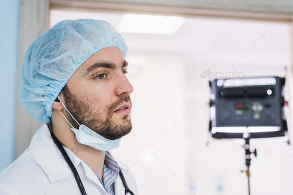 A young handsome pensive man doctor at hospital ward before operation - Stock Photo - Images