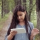 Portrait. A Beautiful Girl Is Walking in Nature Using a Tablet - VideoHive Item for Sale